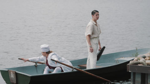 Woman in nurse costume and man in white in boat on lake at pier on sunny day Footage