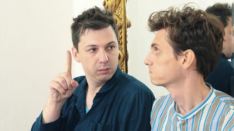 Two worried men sits in white hall at mirror arguing Footage