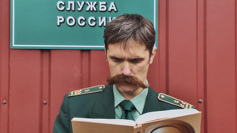 Russian army colonel with big mustaches reading book in front of red wall Footage