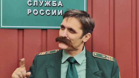 Russian army colonel with big whiskers reading book in front of red wall Live Action