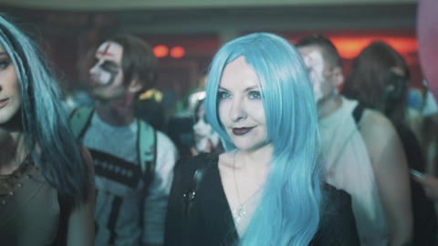 Girl wearing long blue hair wig in crowd of people at night club halloween party Live Action
