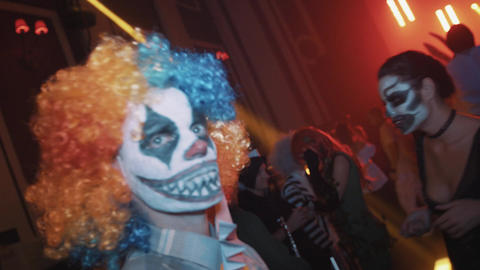 Scary clwn looking directly in camera at night club halloween party Footage