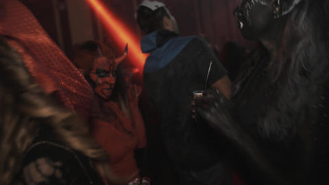 Two girls as devil characters dance in crowd at night club halloween party Footage