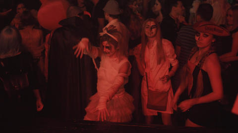 Girl in mummy zombie costume dance in crowd at night club halloween party Footage
