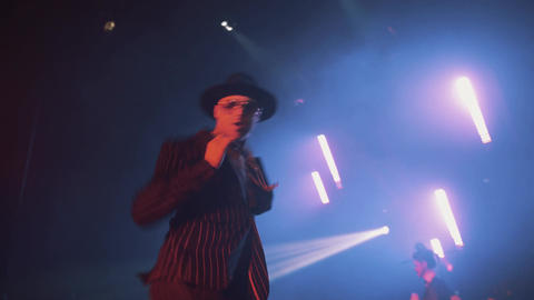 Guy parodying italian artist Adriano Celentano, dancing on scene at night club Footage