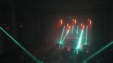 Crowd dance at concert with fast moving beams of light at halloween party Live Action