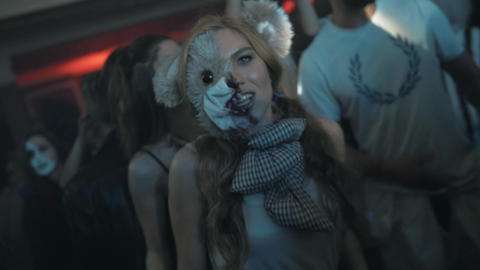 Girl in scary toy animal half mask dance in crowd at night club halloween party Footage