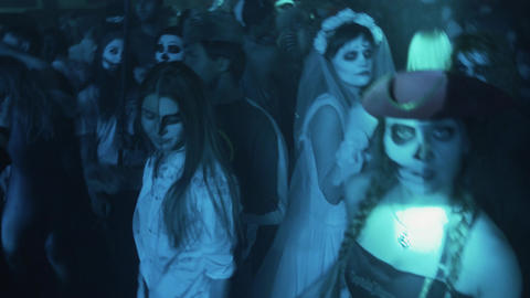 Bunch of costumed young people with face paint dance at halloween party Footage