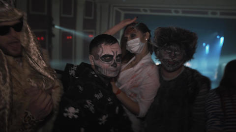 Group of young people in halloween costumes dancing for camera at night club Footage