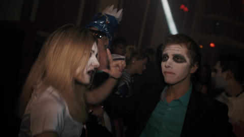Girl in zombie nurse costume dance in crowd at night club halloween party Footage