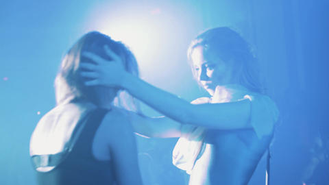 Two girls silhouettes dance on scene at night club in beams of bright light Footage