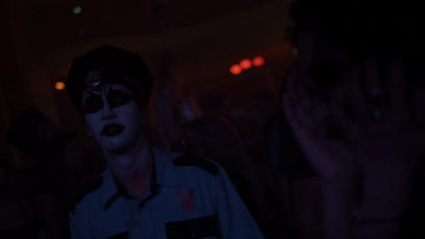 Man in zombie police officer dance in crowd at night club halloween party Footage