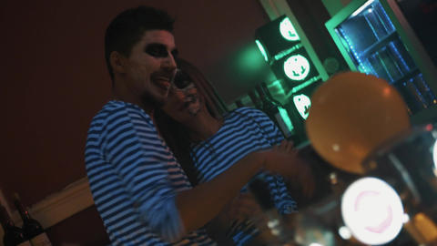 Guy an girl bartenders in stripe shirts and face paint have drinks and laughing Footage