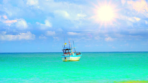 Lovely small fishing vessel swaying on waves of azure ocean against blue sky Footage
