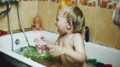 Little boy enjoy water in bathtub. Baby swim in inflatable circle. Splashing Footage