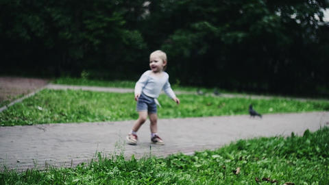 Happy little boy running on playground in summer park. Flying doves. Mother Footage