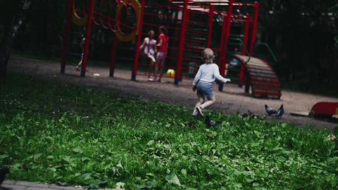 Blonde little boy running on playground in summer park scare doves. Kids Filmmaterial
