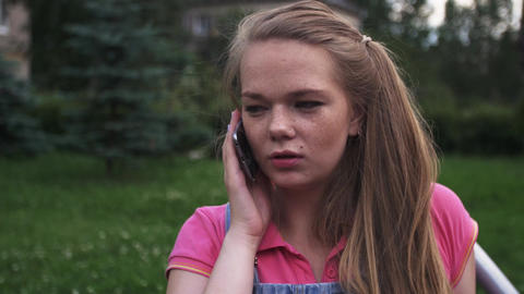 Young attractive girl with freckles speak to phone on bench. Summer park. Smile Footage