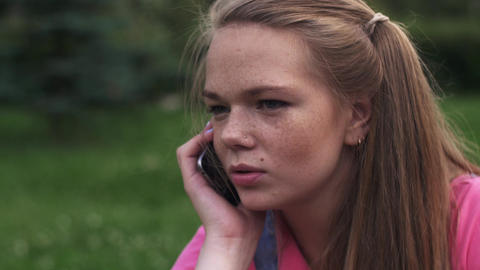 Young attractive girl with freckles speak to phone. Summer park. Portrait Footage