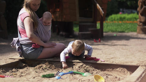 Young mother hold baby in sling, playing with son in sandbox. Playground Footage