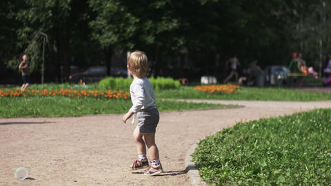 Little boy on playground. Sunny day. Family. Mother with baby on hands. Walking Footage