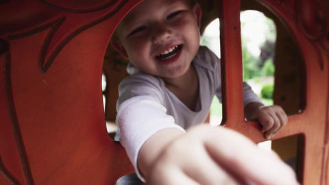Little boy smile in camera from wooden home on playground. Summer day. Walking Footage