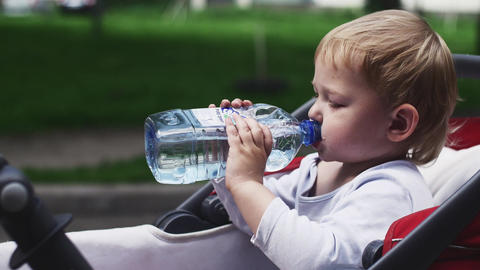 Little boy drink water from bottle in baby carriage on street. Summer. Mother Footage