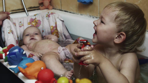 Happy little boy play with toys in bathtub. Baby swim in cradle. Water. Children Footage