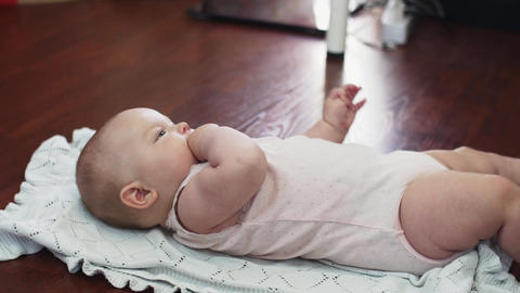 Young mother make push ups and kiss baby lie on floor. Apartment. Motherhood Footage