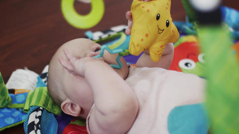 Cute baby lie in crib playing with toys, holding in mouth. Cute. Motherhood Footage