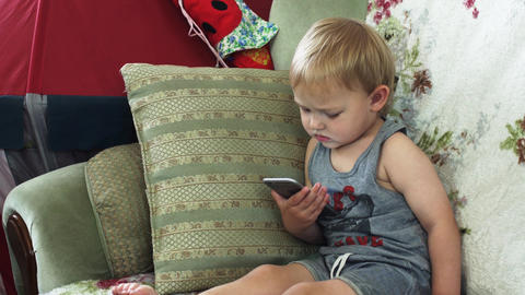 Blonde little boy sitting on sofa in apartment with smartphone. Childhood Footage