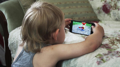 Little boy on sofa watching video on smartphone. Childhood. Device. Internet Footage