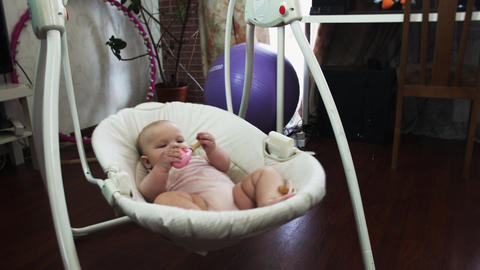 Adorable little baby sway on swing in apartment. Pink toy in hands. Dummy Footage