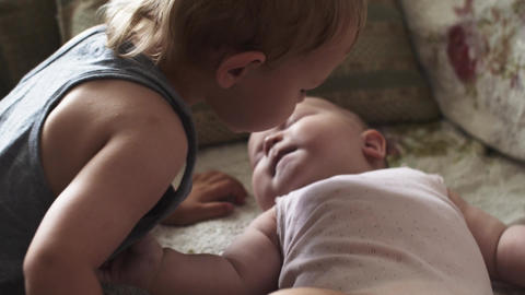 Little blonde boy kiss baby lie on sofa. Children. Love. Brother. Sister. Family Footage