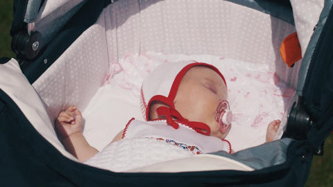 Little baby sleep in baby carriage. Baby dummy.Summer sunny day. Motherhood Footage