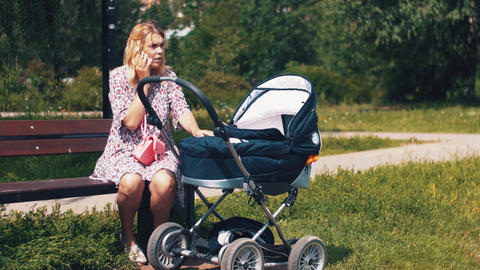 Mother sway baby carriage and speaking on phone in summer park. Sunny day Footage