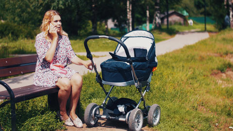 Mother sway baby carriage and speaking on phone on bench in summer park. Sunny Footage
