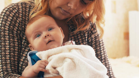 Mother sitting with little cute baby on hands. Mothering. Baby has blue eyes Footage