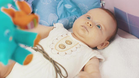 Little baby lie in crib. Colorful moving toys. Childhood. Motherhood. Mothering Live Action