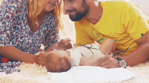 Happy young parents communicate with little baby. Family. Father and mother kiss Footage
