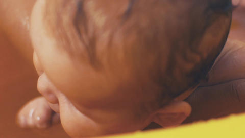Mother bathing little baby with blue eyes. Yellow bath. Motherhood. Love. Care Footage