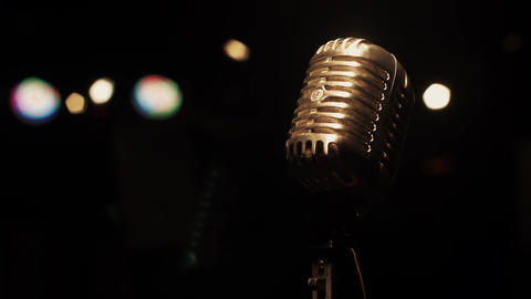 Concert metal glowing microphone stay on stage in empty retro club. Spotlights Footage