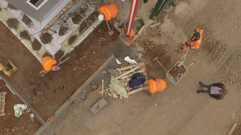 Upper View Workers Dig Hole and Load Ground in Wheelbarrow Footage
