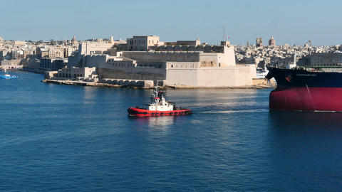 pilot tag boat pulling cargo ship with with nice Valletta fortress view Footage