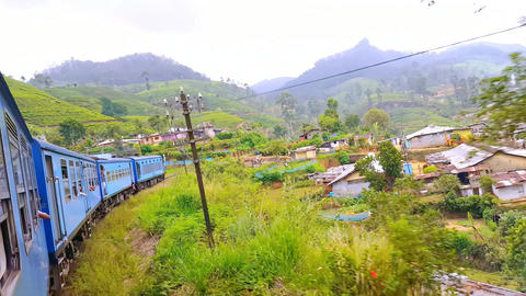 Train passing small village with houses and farm fields at tea plantations. Trad Footage