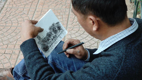 The street artist draws a picture with pencils Footage