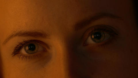 4K Winking Young Woman Eyes Close-Up Under Warm Low-Key Lighting Footage
