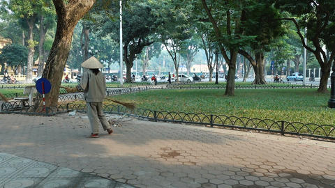 Person sweeps streets of Hanoi Footage