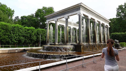 Tourist girl walk forward and take photo of gorgeous fountain building