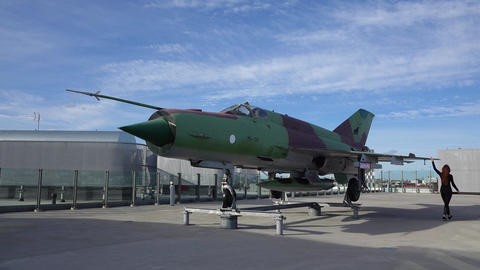 Mig-21 jet fighter aircraft at for display at roof, girl come and touch wing Live Action